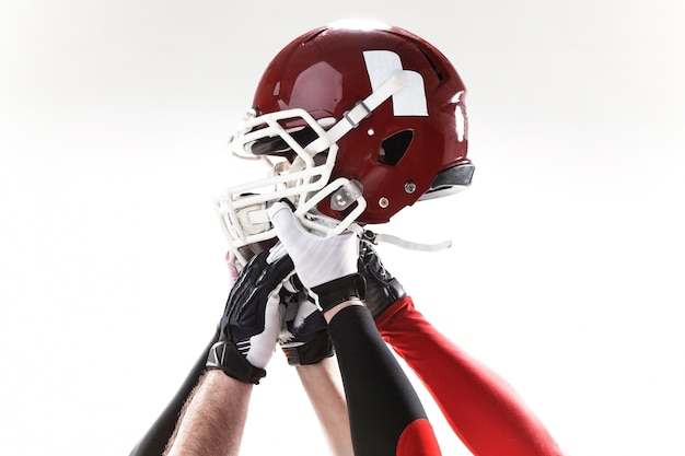 白い背景の上のヘルメットとアメリカンフットボール選手の手