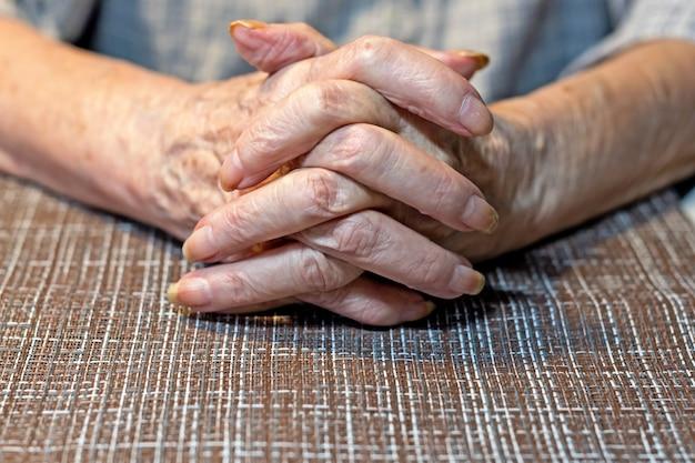 テーブルの上で休んでいる年配の女性の手。パーキンソン。