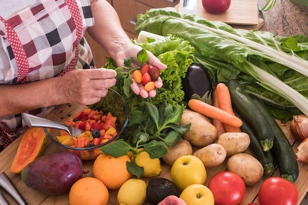 노파의 손이 과일을 자르고 가장 좋은 작은 토마토를 찾습니다. 다채로운 과일과 야채의 큰 그룹과 함께 나무 테이블. 건강한 식사