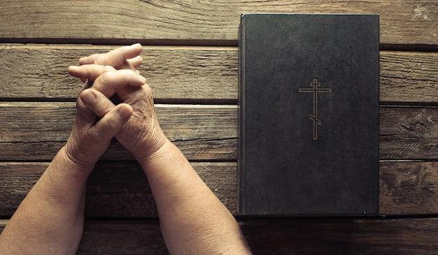 古い素朴なボード上の聖書の本の近くに年配の女性の手が祈ります。宗教の概念