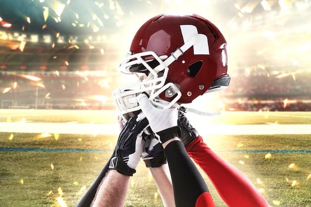 スタジアムの背景にヘルメットを持つ5人のアメリカンフットボール選手の手