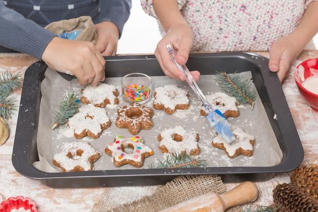 男の子と女の子の手がクリスマスのクッキーを飾ります