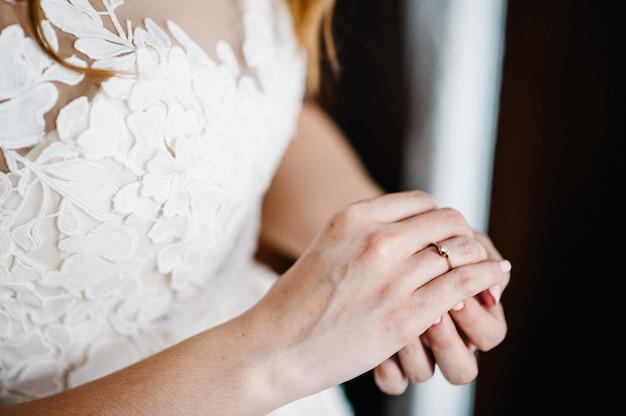 金の婚約指輪をダイヤモンドで身に着けて修正する花嫁の手。花嫁の準備。結婚式の朝。宝石。マニキュアのクローズアップ。