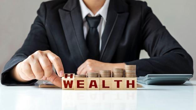 ビジネスマンの手は、正方形、正方形、健康と富をひっくり返します。金銭的富、生命の概念および健康保険への投資