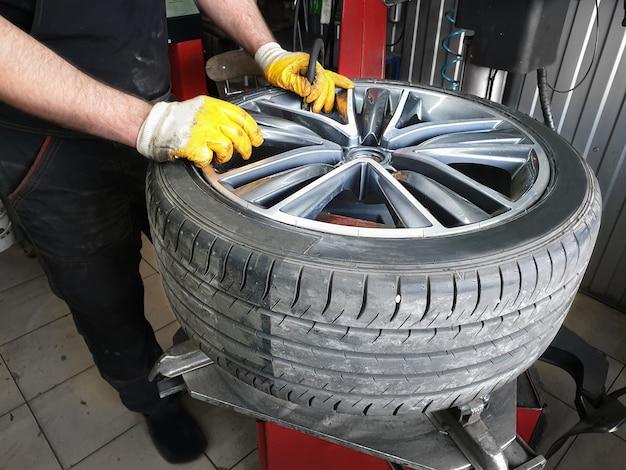 タイヤでホイールを握っている自動車整備士の手。