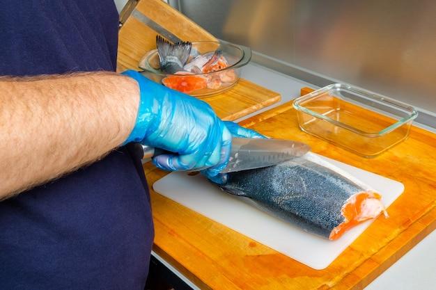 Руки повара в перчатках режут ножом туловище лосося