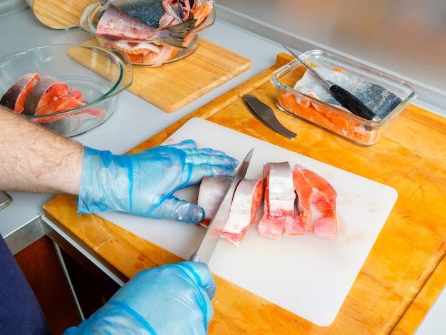 위생 장갑을 낀 요리사의 손이 칼로 핑크 연어의 몸을 자른다