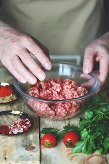 料理人の手が生のひき肉をボウルに入れてかき混ぜます