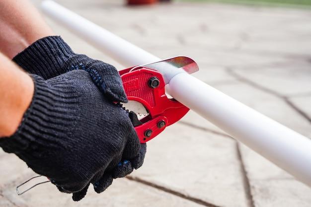 В руках мастера держат ножницы по металлу для резки пластиковых водопроводных труб снаружи.