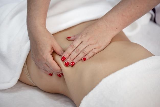 안마사의 손은 여성에게 요추와 엉덩이의 편안한 마사지를 제공합니다.