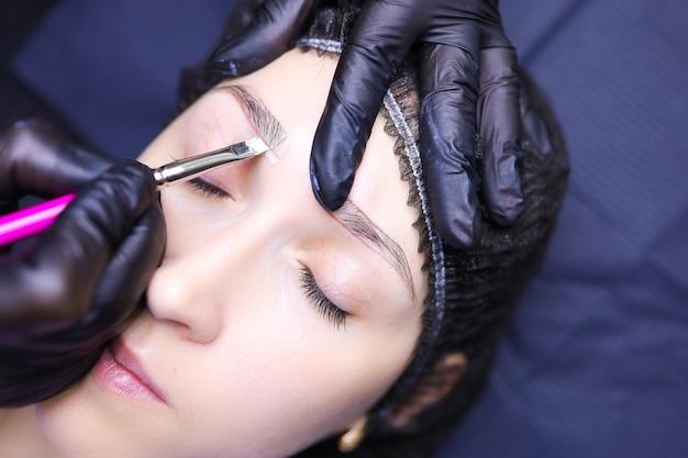 Руки татуировщика крупным планом подчеркнем контур бровей кисточкой