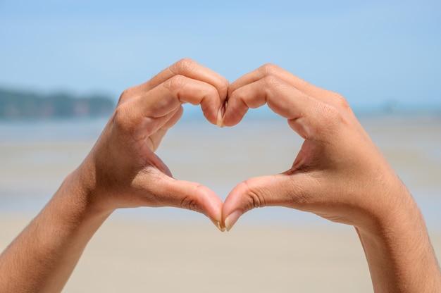 女性と男性の手はハート型で、太陽光が手の中を通ります