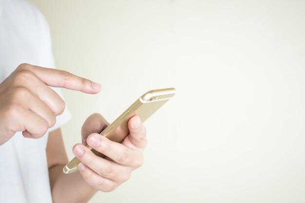 흰 셔츠를 입은 여성의 손이 전화로 소셜 미디어를 사용하고 있습니다.
