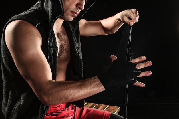 黒の筋肉男トレーニングキックボクシングの包帯で手
