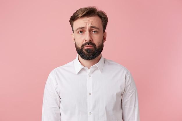 ハンサムなあごひげを生やした男は眉をひそめ、カメラを悲しげに見ます、彼は不快なニュースを言われました。ピンクの背景に分離。