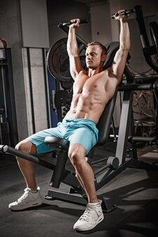 ジムでハンサムなフィットネス男重量挙げトレーニング