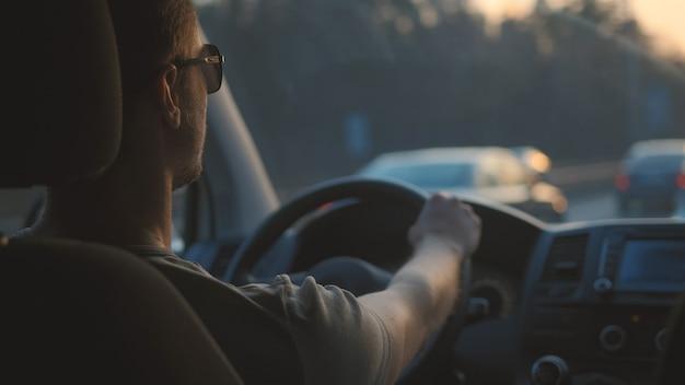 ハンサムな男は高速道路に沿って車を運転します
