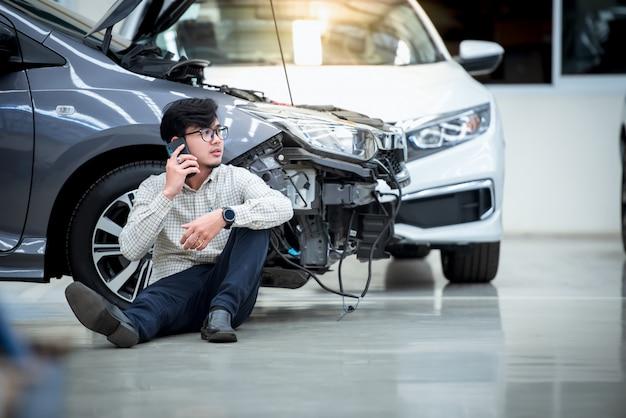 ハンサムな男は、損傷した車が事故に遭った後、ストレスの多いジェスチャーをし、車が道路に衝突した後、電話を使って助けを求めました。車は傷害保険に加入しています。