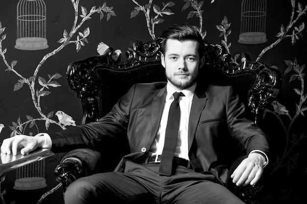 灰色のスーツを着たハンサムな男。インテリアの青年実業家の肖像画。成功した青年実業家の肖像画。