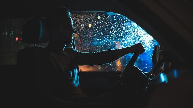 잘 생긴 남자는 밤 비오는 거리에 차에 앉아있다