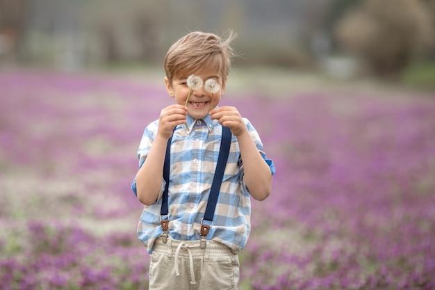 격자 무늬 셔츠와 아름다운 헤어 스타일에서 가장 행복한 아이가 봄 정원에서 산책