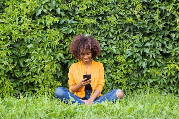 電話で話している通りで幸せなアフリカ系アメリカ人の女性