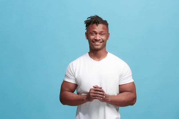 Счастливый афро-американский деловой человек, стоящий и улыбающийся на синем фоне.