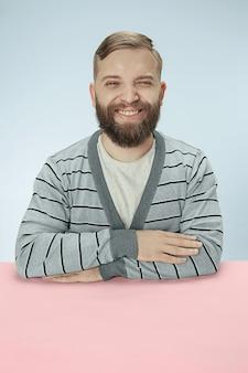 青いスペースのテーブルに座って幸せで笑顔のビジネスマン