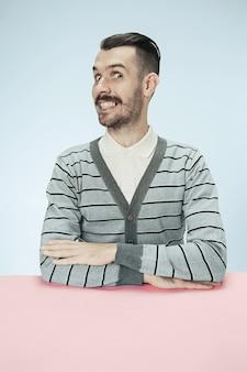 블루 스튜디오 배경에 테이블에 앉아 행복 하 고 웃는 비즈니스 사람. 미니멀리즘 스타일의 초상화
