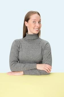 ピンクのスタジオの背景にテーブルに座って幸せで笑顔のビジネス女性。ミニマリズムスタイルの肖像画