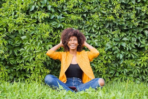 Счастливая и молодая афро-американская женщина на улице весело