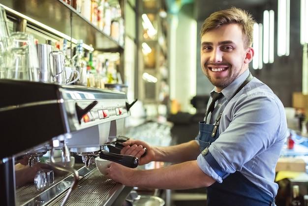 바에서 커피 머신을 가지고 일하는 행복한 바리스타