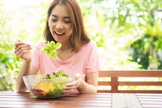 バルコニーに座っている幸せな美しいアジアの健康な中年女性