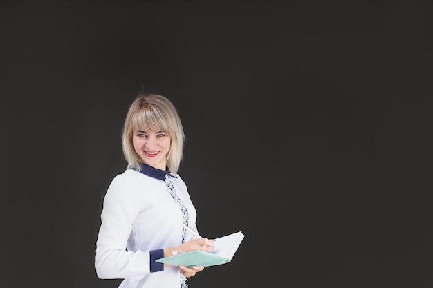 Счастливая блондинка, учительница на фоне черной стены