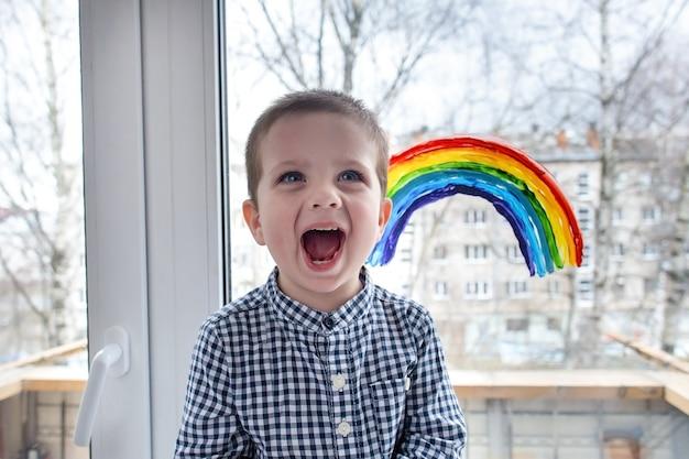 집에서 행복한 소년은 창문에 무지개를 그렸습니다.