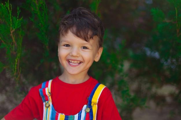 Счастливый мальчик смеется. ребенок в красной футболке и ярком комбинезоне на улице, на фоне зеленой ели.