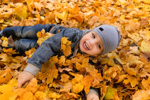 Счастливый мальчик играет в осенней листве
