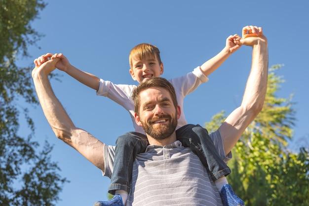 Счастливый мальчик сидит на шее отца