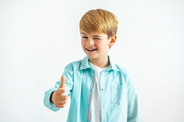幸せな男の子は白い背景に親指を立てる