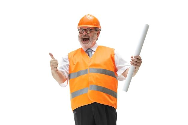 建設ベストとスタジオで笑っているオレンジ色のヘルメットの幸せなビルダー