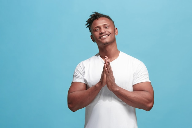 幸せなビジネスアフリカ系アメリカ人の男が立って、青い壁に笑みを浮かべて