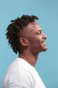 幸せなビジネスアフリカ系アメリカ人の男が立って、青に対して笑顔します。