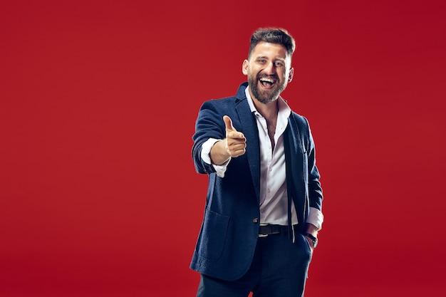 幸せなビジネスマンはあなたを指して、赤い壁に半分の長さのクローズアップの肖像画を望んでいます