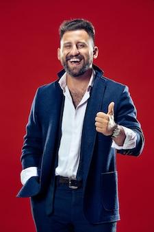 Счастливый деловой человек стоит и улыбается у красной стены