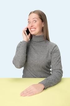 ピンクの背景に携帯電話で座っている幸せなビジネス女性。