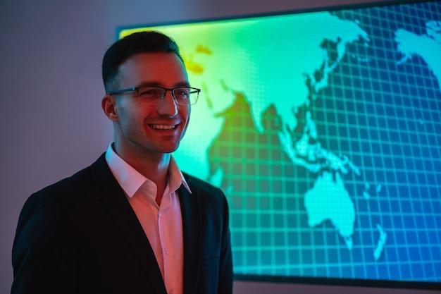 Счастливый бизнесмен в очках, стоящий возле большого дисплея