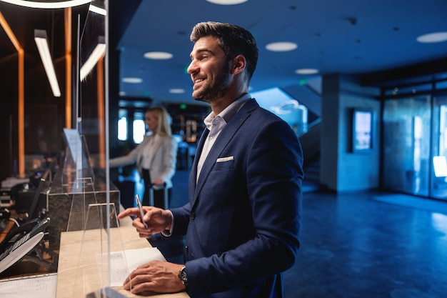 幸せなビジネスマンはホテルの受付に立ち、フォームに記入して署名することで登録します。出張、平日、ライフスタイル