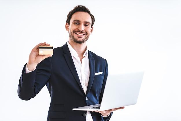白い背景の上のクレジットカードとラップトップを持つ幸せな実業家