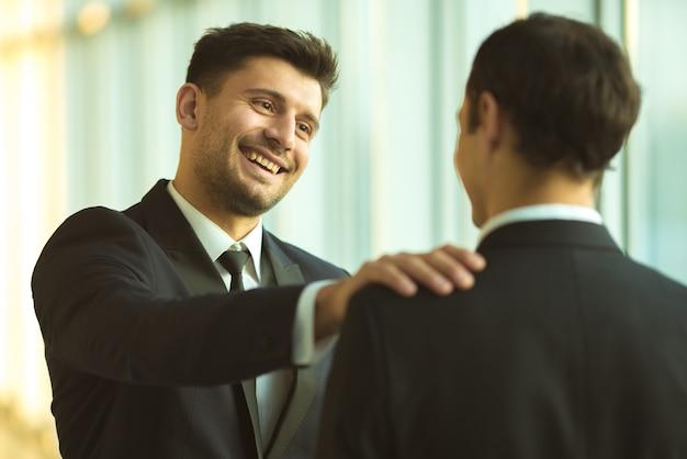 행복한 사업가들이 사무실에서 어깨를 두드린다