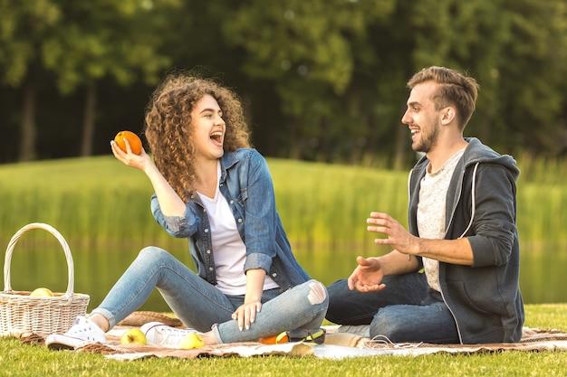 公園の芝生の上で楽しい幸せなカップル